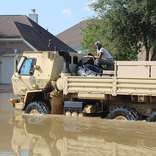 Image of national guard vehicle traversing a flooded street