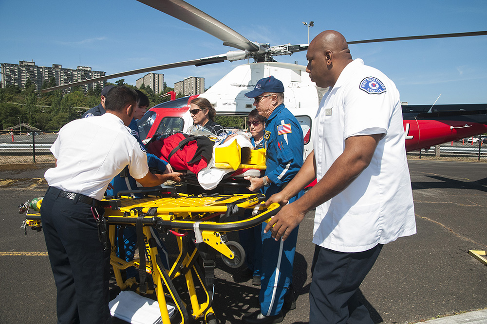 Airlift Northwest flight nurses and Seattle Fire Department paramedics stabilizing and transporting a patient at Graves Field, Seattle, WA