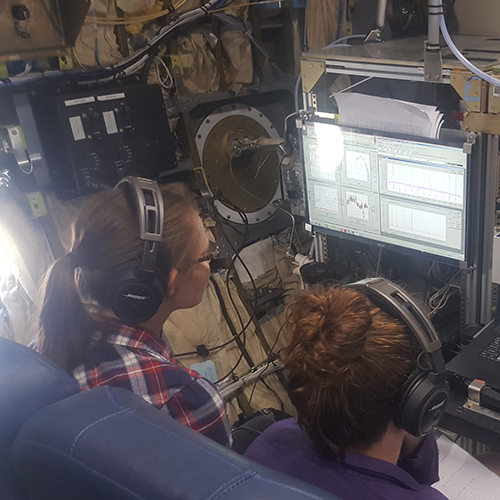 Researchers look at incoming data inside the research aircraft