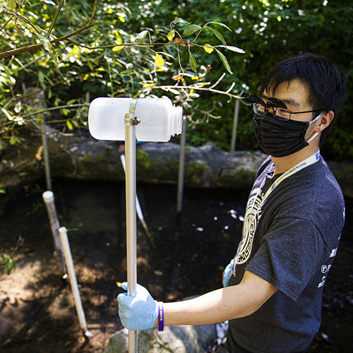 Image of a student holding a sampling pole that is used to collect creek water