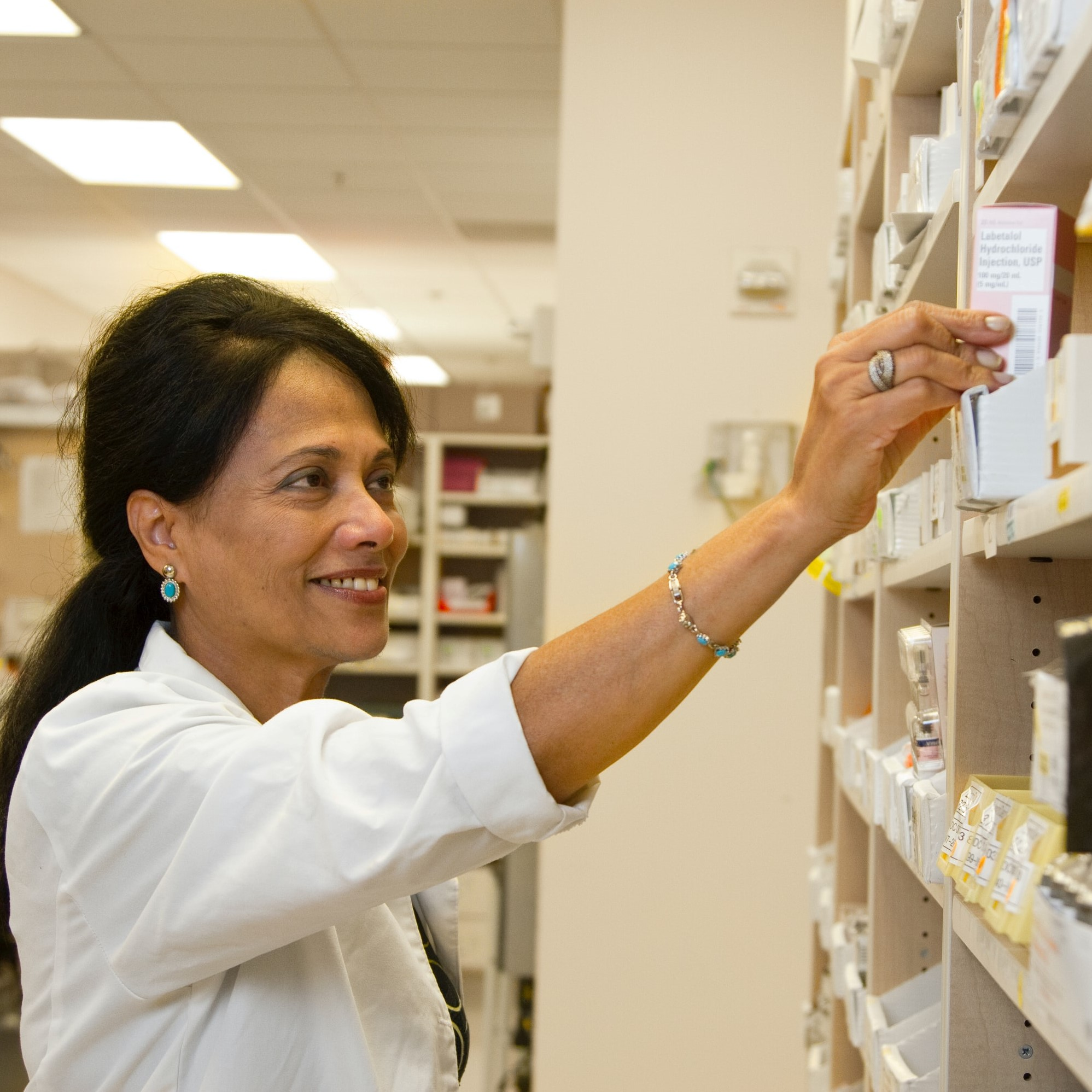 Image of a pharmacist reaching for a box