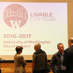 people in front of a large screen during a meeting of Livable City Year