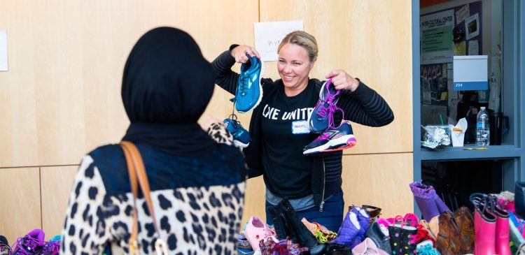 A person holds shoes at a Family Resource Exchange event