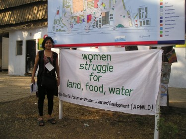 international work: Woman with sign that reads 'women struggle for land, food, water