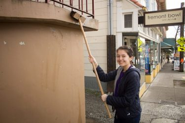A person paints a wall outside.