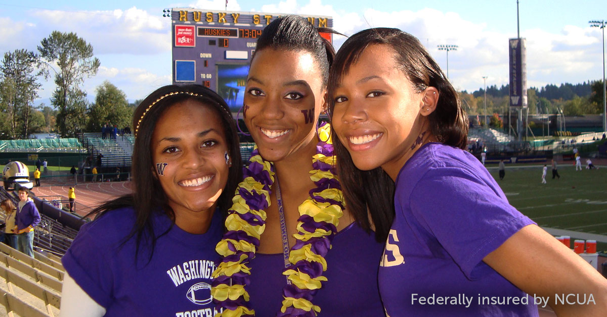 Three women pose for a photo in the stands of Husky Stadium
