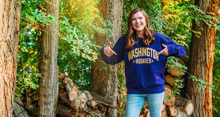 Hannah Doyle, a Unite UW participant, smiling while walking in the woods in a UW sweatshirt