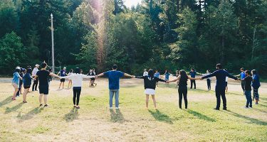 Students holding hands in a circle in a field near the woods at a Unite UW retreat