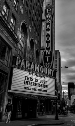 "A black-and-white photo of the Paramount Theater entrance. Its marquee reads: ""This is just intermission. We'll see you soon."""