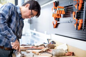 Sven Haakanson, a curator of Native American anthropology at the Burke Museum, works with artifacts at a lab bench.