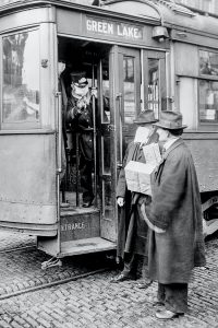 Two men talking to conductor on a trolley to Green Lake in the early 1900s