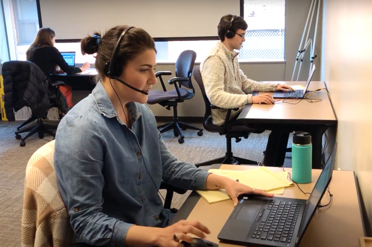 woman wearing headphones, sitting in front of computer, two other people in background
