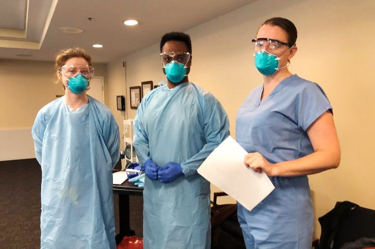 Emily Ford, Chase Cannon, Jenelle Stewart, wearing medical scrubs, goggles and masks