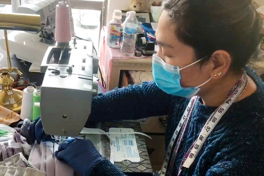 A woman wearing a mask operating a sewing machine