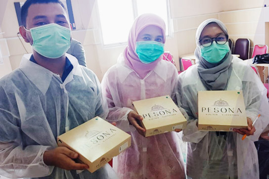 A man and two women wearing masks and holding gold boxes labeled Pesona