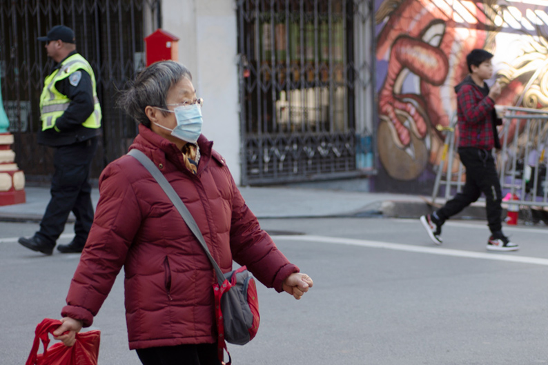 Older Asian woman wearing a medical mask, walking down the street