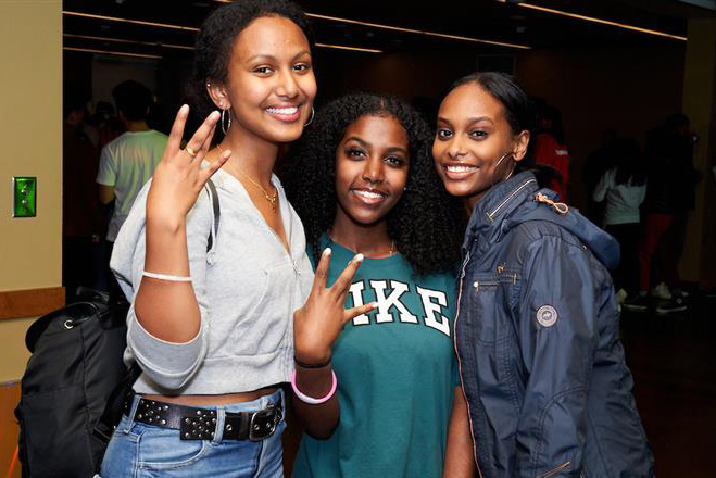 three Black female students standing close together and smiling