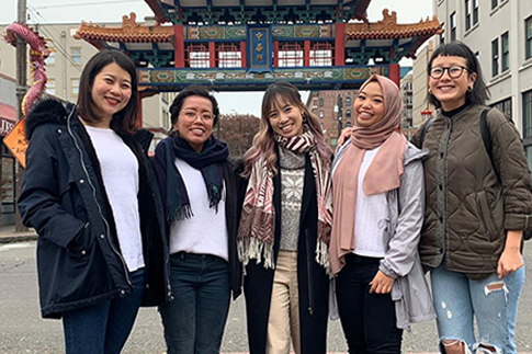 five young women standing in front of Chinatown gate in Seattle