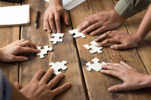 Multiple hands working on a jigsaw puzzle