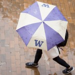 Student walking with UW umbrella