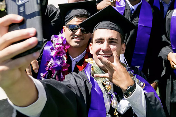 two male graduates in caps and gowns taking a selfie with a phone