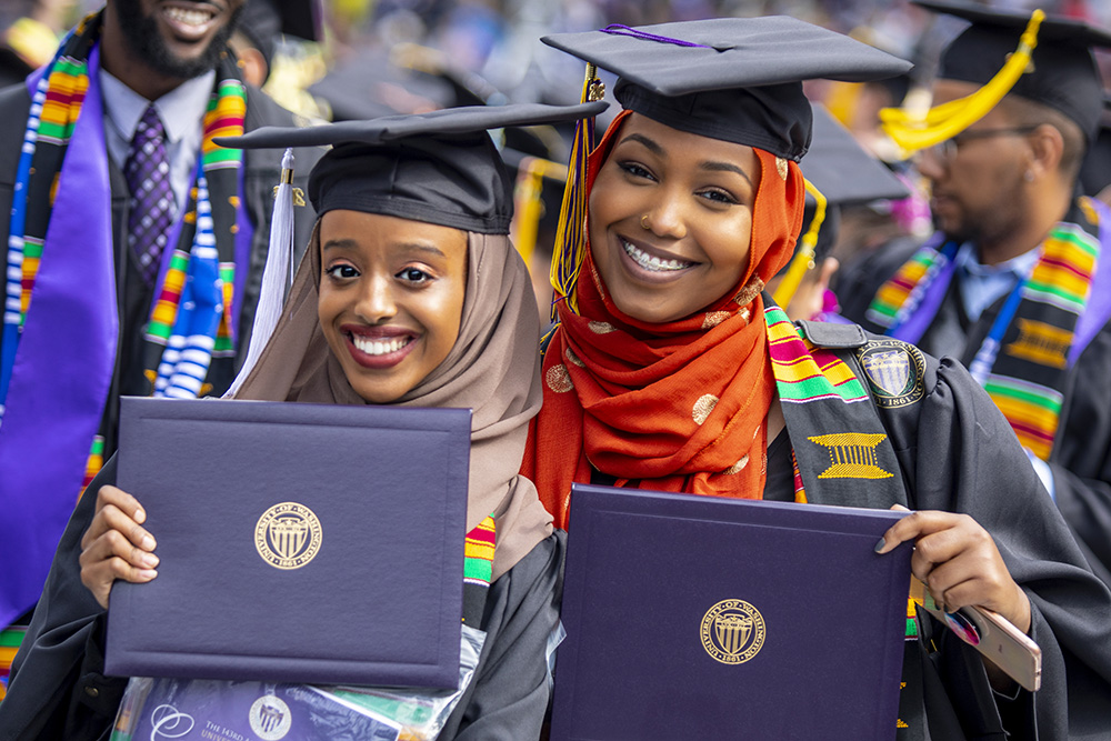 two women in graduation caps and gowns worn with hijabs and kente cloth stoles holding up their UW diploma cases