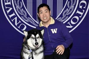man in purple W jacket kneeling next to official UW Husky dog mascot