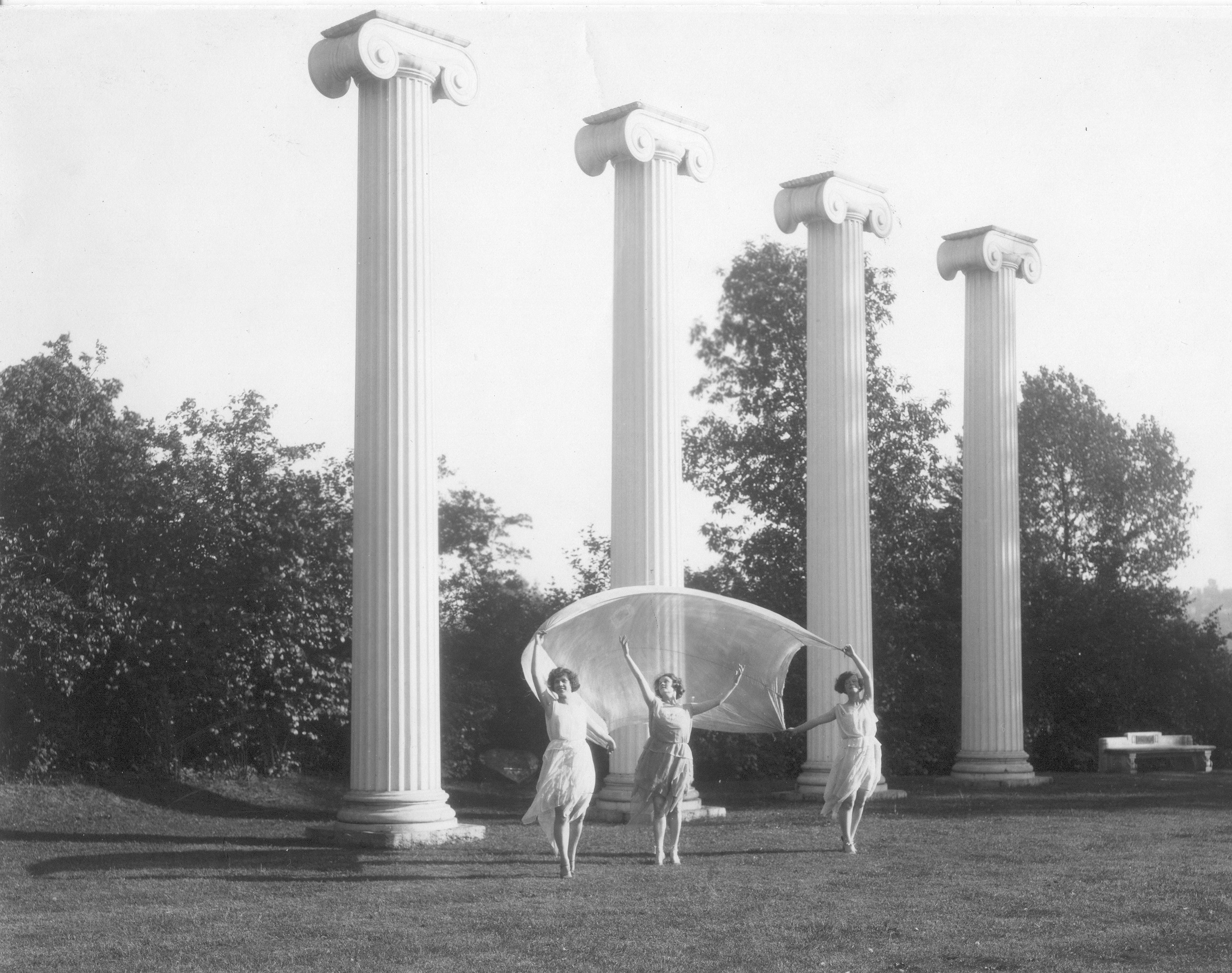 Three 1920's women dance in Sylvan Grove in front of the Four Columns