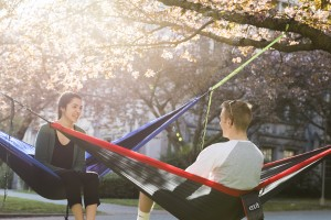 UW students enjoying the sun a on hammock at Rainier Vista.