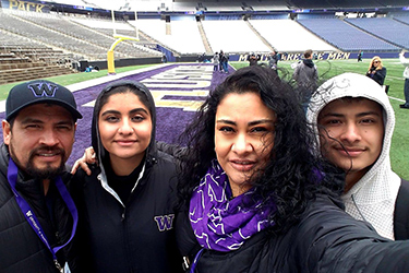 a family posing for a selfie at the Husky Stadium