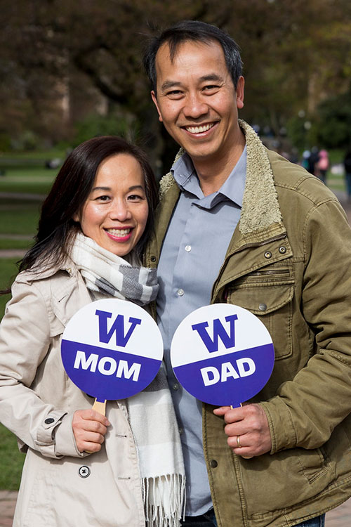 Two people hold W mom and W dad signs