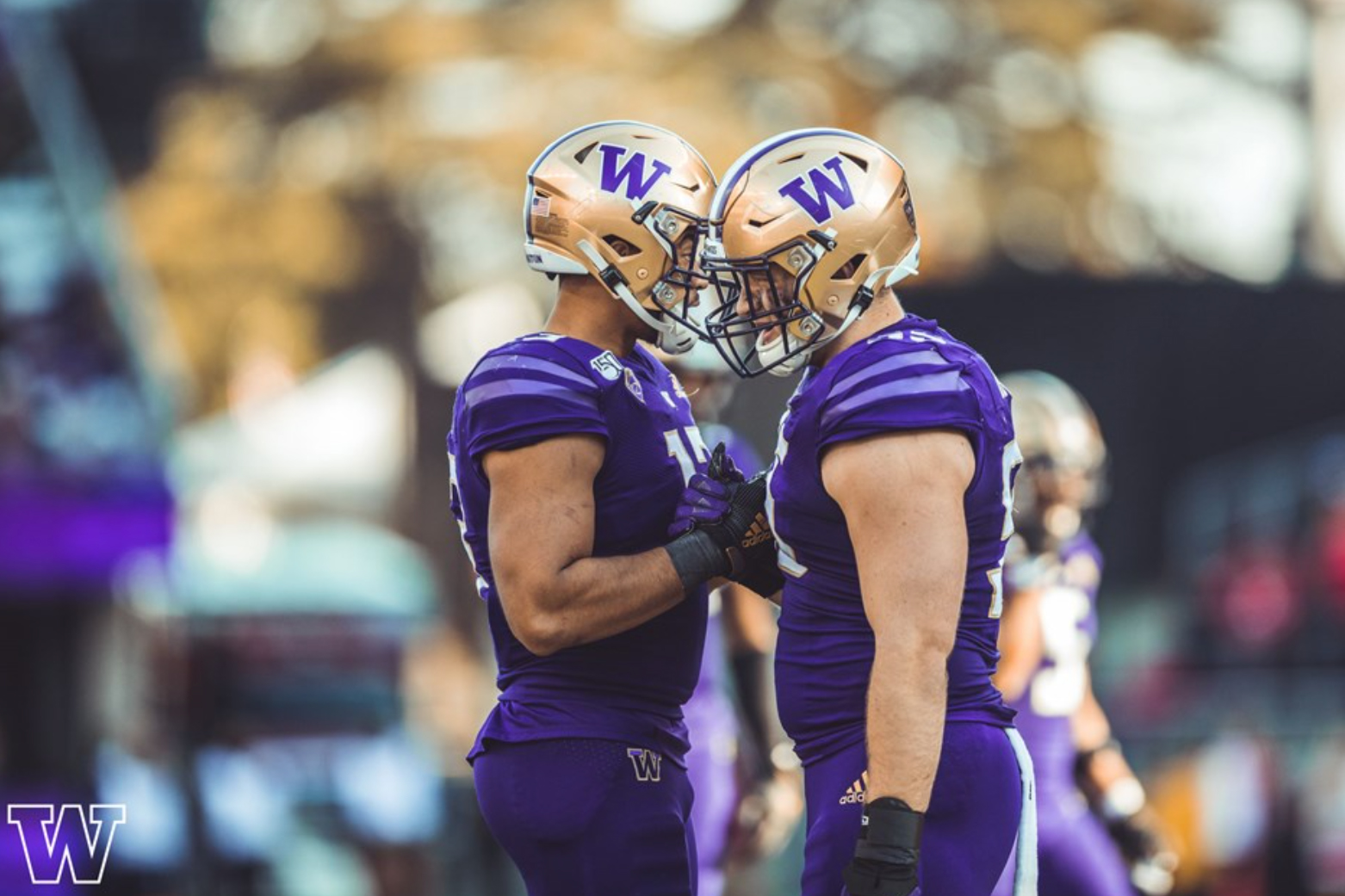 two University of Washington football players clasping hands