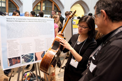 Lee Gee discusses sustainable production of classical guitars at a poster session