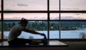 a women stretching near a mountain-view window