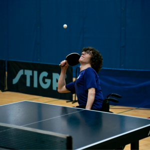 A table tennis player focuses on the ball while playing from a wheelchair as a part of our Rec Clubs.