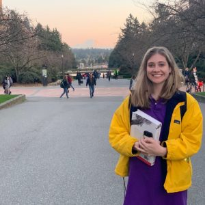 A photo of Cassie Taylor holding a book on the UW Seattle campus with Mount Rainier in the background.