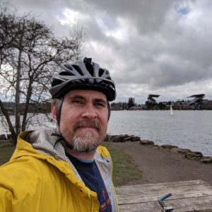 A photo of Greg Barnes on his bike with Husky Stadium in the background.