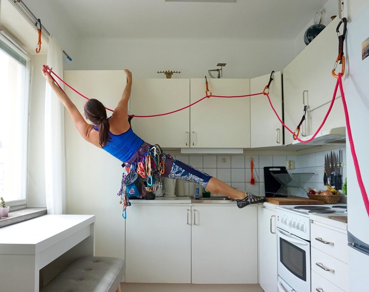 UW alumna Nicole Savage rock climbs her kitchen cabinets.