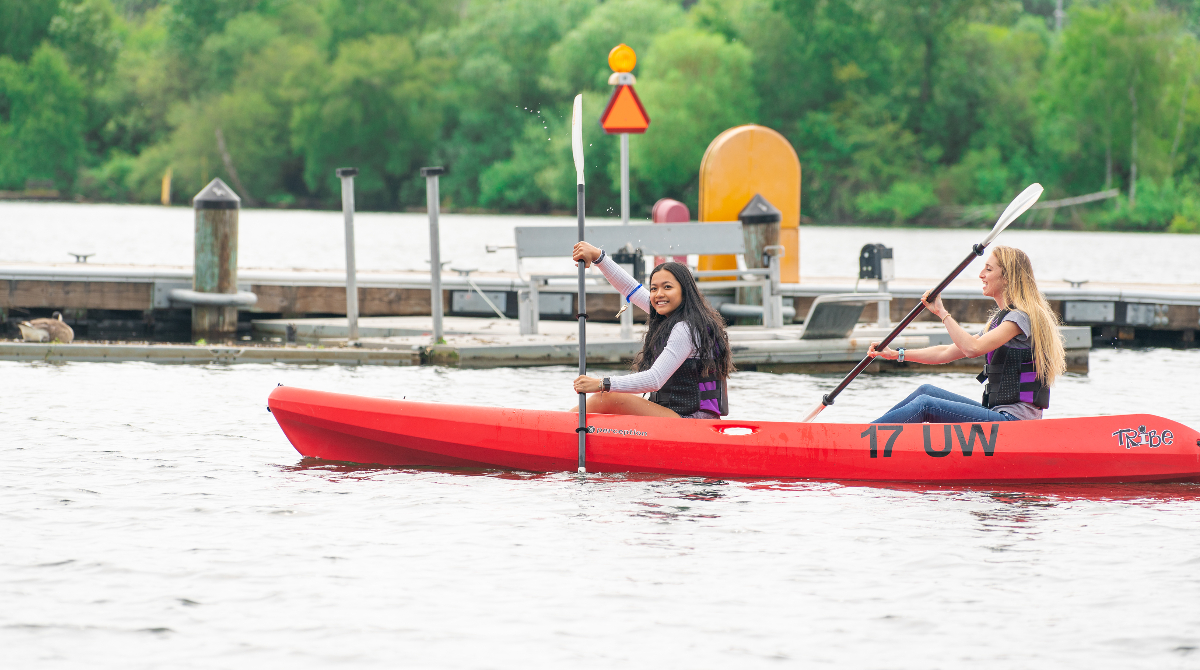 Students paddle in a two-person kayak from the Waterfront Activities Center.