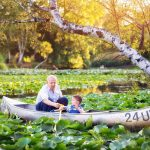 An older gentleman and a child paddle in a UW canoe.