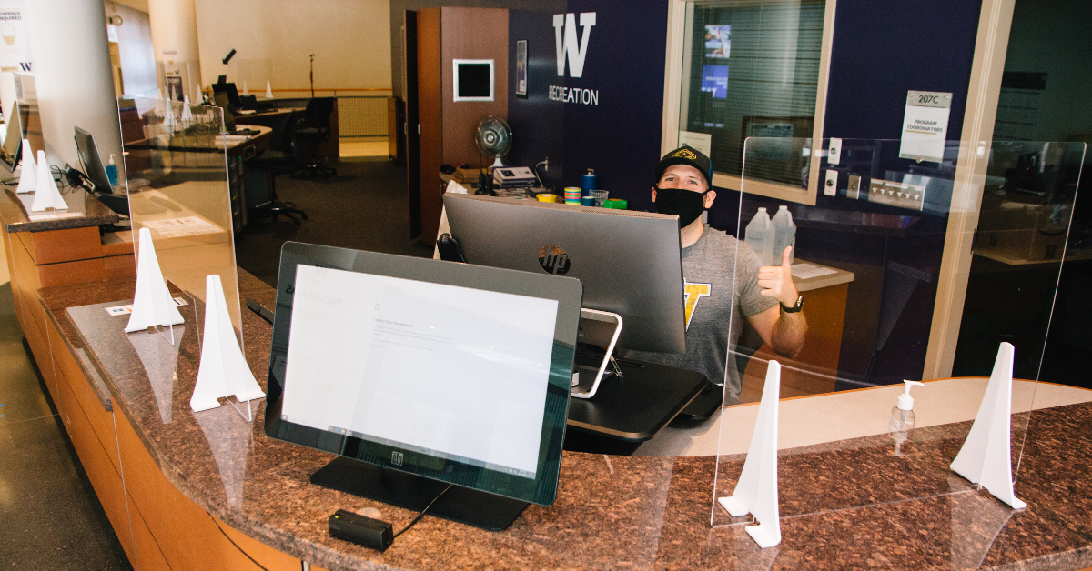 A man wearing a face covering sits at the membership desk at the IMA giving a thumbs up