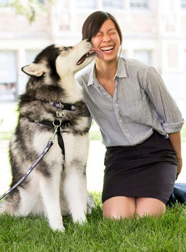 UW mascot Dubs licks the face of a smiling woman.