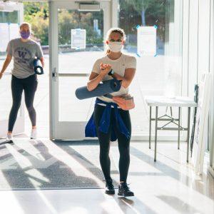 Two women enter the IMA carrying yoga mats.