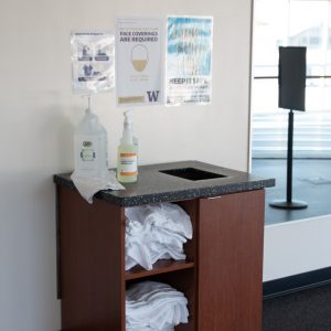 A hand sanitizer station and cleaning supplies at the IMA