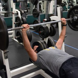 A man lifts a barbell with weights while wearing a mask.