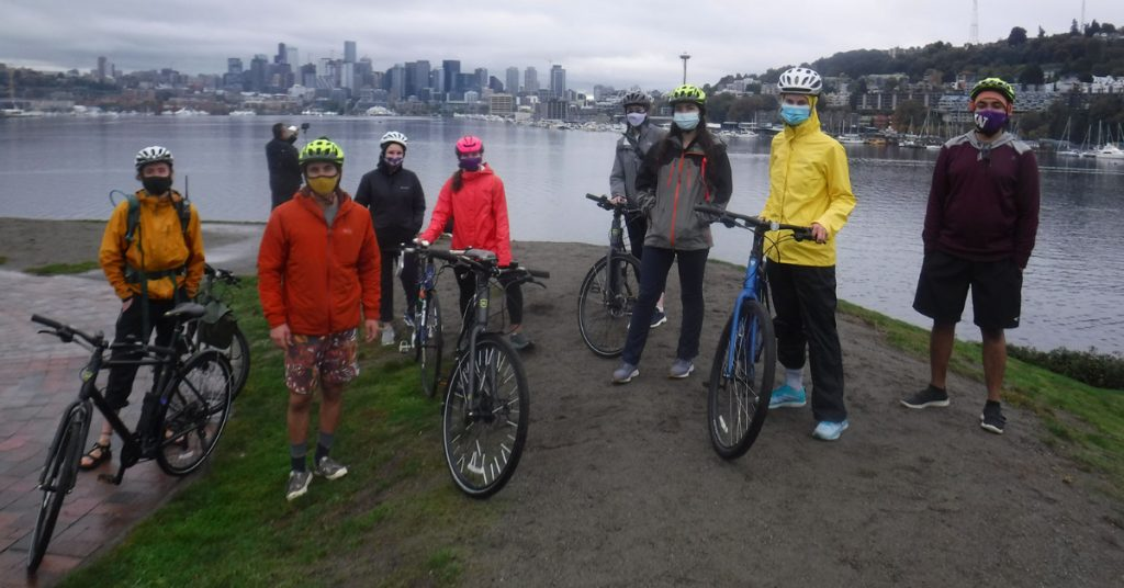 A group of masked students stands with their bikes in front of Lake Union and the Space Needle.