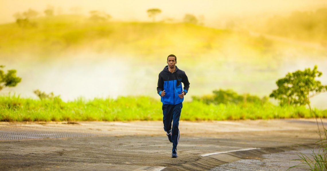 A man runs in workout clothes with a bright yellow background and greenery behind him.