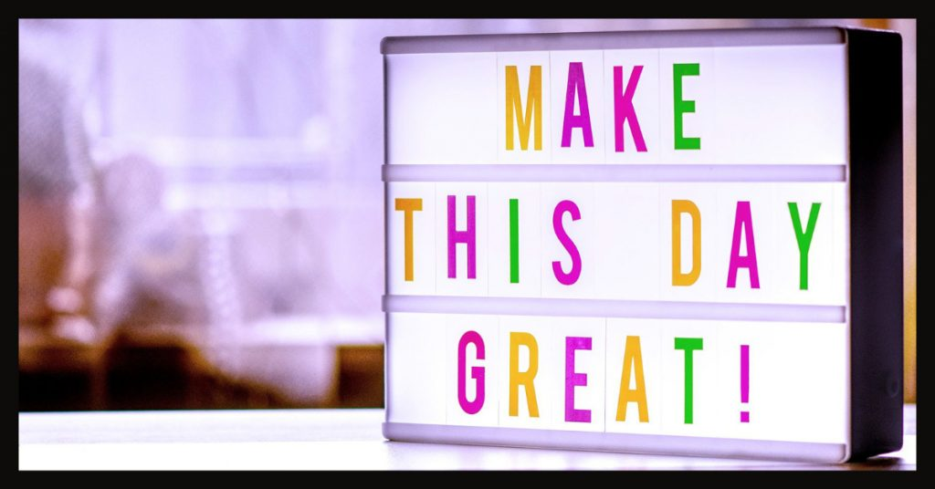 A photo of a brightly-colored sign that reads: Make this day great!