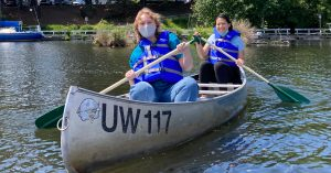 Two students smile from within a canoe on the water marked UW.