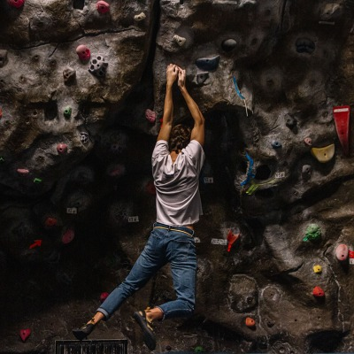 A climbing participant hangs by their hands on the climbing wall.